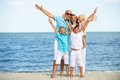 Smiling family with children having fun on the beach portrait of sunny raised hands Stock Photo