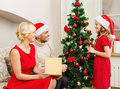 Smiling family decorating christmas tree x mas winter happiness and people concept in santa helper hats Royalty Free Stock Image