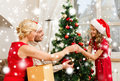 Smiling family decorating christmas tree x mas winter happiness and people concept in santa helper hats Royalty Free Stock Images