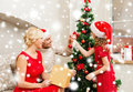Smiling family decorating christmas tree x mas winter happiness and people concept in santa helper hats Royalty Free Stock Photos