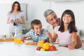 Smiling family eating breakfast in kitchen together Royalty Free Stock Photo