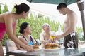 Smiling family eating hamburgers by the pool on vacation Royalty Free Stock Image