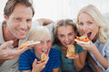 Smiling family eating pizza and looking at camera Royalty Free Stock Photo