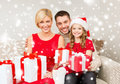 Smiling family holding many gift boxes christmas x mas winter happiness and people concept in santa helper hats with Stock Images