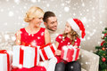 Smiling family holding many gift boxes christmas x mas winter happiness and people concept in santa helper hats with Royalty Free Stock Image