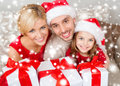 Smiling family holding many gift boxes christmas x mas winter happiness and people concept in santa helper hats with Stock Photos