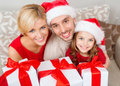 Smiling family holding many gift boxes christmas x mas winter happiness and people concept in santa helper hats with Stock Photo