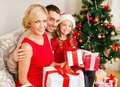Smiling family holding many gift boxes christmas x mas winter happiness and people concept in santa helper hats with Royalty Free Stock Photography