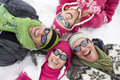 Smiling family laying in snow in circle together Stock Image