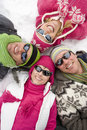 Smiling family laying in snow in circle together Royalty Free Stock Photos