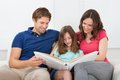 Smiling family looking at photo album Royalty Free Stock Photo