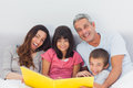 Smiling family looking together at their photograph album in bed Royalty Free Stock Photo