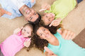 Smiling family lying on the rug in a circle showing thumbs up at home living room Stock Photo
