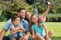 Smiling family in a park taking photos the sunshine Stock Photo