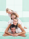 Smiling family piled on top of dad the bed Royalty Free Stock Photography