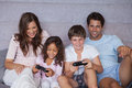 Smiling family playing video games on bed Stock Photography