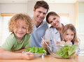 Smiling family preparing a salad together Royalty Free Stock Images