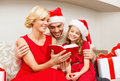 Smiling family reading book christmas x mas winter happiness and people concept in santa helper hats with many gift boxes Royalty Free Stock Photos