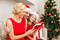 Smiling family reading book christmas x mas winter happiness and people concept in santa helper hats with many gift boxes Royalty Free Stock Image