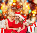 Smiling family reading postcard christmas x mas winter happiness and people concept in santa helper hats with many gift boxes Royalty Free Stock Image