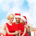 Smiling family reading postcard christmas x mas winter happiness and people concept in santa helper hats with many gift boxes Stock Photo