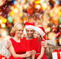 Smiling family reading postcard christmas x mas winter happiness and people concept in santa helper hats with many gift boxes Royalty Free Stock Photos