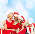 Smiling family reading postcard christmas x mas winter happiness and people concept in santa helper hats with many gift boxes Royalty Free Stock Images