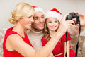 Smiling family in santa helper hats taking picture christmas x mas winter happiness and people concept with photo camera Royalty Free Stock Images