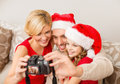 Smiling family in santa helper hats taking picture christmas x mas winter happiness and people concept with photo camera Stock Image