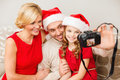 Smiling family in santa helper hats taking picture christmas x mas winter happiness and people concept with photo camera Royalty Free Stock Photos