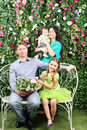 Smiling family sit on white bench with bunch of four of flowers and stand behind in garden near verdant hedge Royalty Free Stock Photo