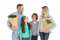 Smiling family standing holding bag of healthy groceries Royalty Free Stock Photo