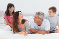 Smiling family talking together on bed at home Stock Images