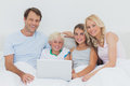 Smiling family using a laptop together in bed Stock Photos