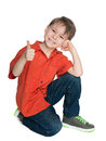 Smiling fashion boy with his thumb up a is sitting on the white background Royalty Free Stock Images