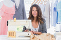 Smiling fashion designer using sewing machine and sitting behind her desk Stock Photo