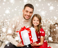 Smiling father and daughter holding gift box family christmas x mas winter happiness people concept Stock Photos