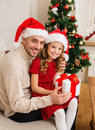 Smiling father and daughter holding gift box family christmas x mas winter happiness people concept in santa helper hats Stock Images
