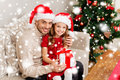Smiling father and daughter holding gift box family christmas x mas winter happiness people concept in santa helper hats Stock Photography