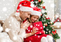 Smiling father and daughter opening gift box family christmas x mas winter happiness people concept in santa helper hats Stock Photography