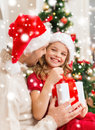 Smiling father and daughter opening gift box family christmas x mas winter happiness people concept in santa helper hats Stock Photos