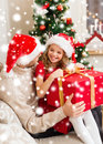 Smiling father and daughter opening gift box family christmas x mas winter happiness people concept in santa helper hats Stock Images