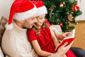 Smiling father and daughter reading book family christmas x mas winter happiness people concept in santa helper hats Stock Images