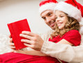 Smiling father and daughter reading book family christmas x mas winter happiness people concept in santa helper hats Royalty Free Stock Images