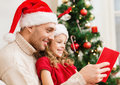 Smiling father and daughter reading book family christmas x mas winter happiness people concept in santa helper hats Stock Photography