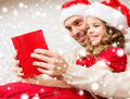 Smiling father and daughter reading book family christmas x mas winter happiness people concept in santa helper hats Stock Photos
