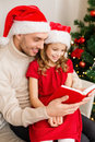 Smiling father and daughter reading book family christmas x mas winter happiness people concept in santa helper hats Stock Image