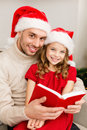 Smiling father and daughter reading book family christmas x mas winter happiness people concept in santa helper hats Royalty Free Stock Photo