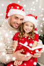 Smiling father and daughter reading book family christmas x mas winter happiness people concept in santa helper hats Royalty Free Stock Photos