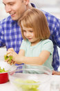 Smiling father and little girl at kitchen family child food home concept cooking salad Royalty Free Stock Photo